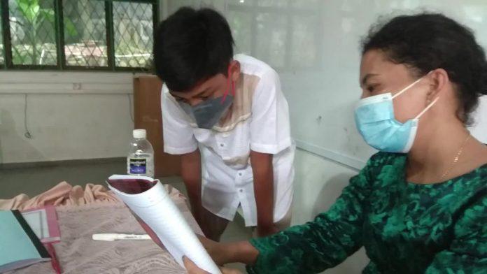 Guru SMPN 6 Batam menjelaskan pada salah seorang siswa yang kurang paham terhadap materi yang diajarkan saat PTM berlangsung pada hari kedua. Kamis (23/9).